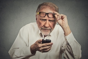 Presbyopic man with glasses having trouble seeing cell phone has vision problems
